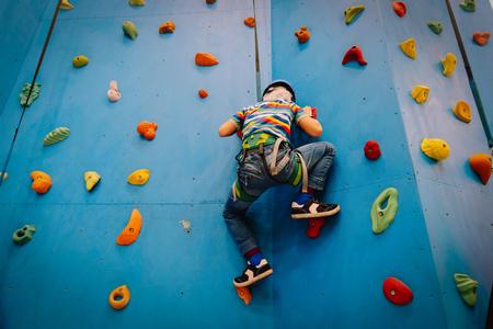 Petit garçon escalade mur dans le centre de sport Banque d'images - 91091016