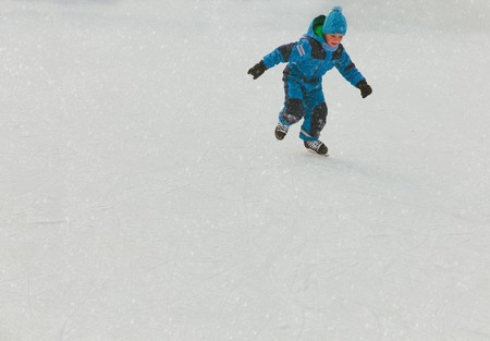 little boy skating on ice in winter