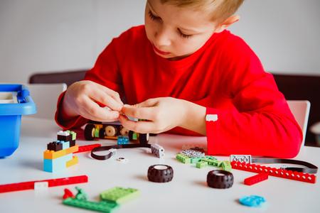 kleine jongen bouwrobot op robot technologie les