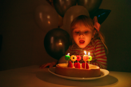 little girl make wish blow candles at birthday party