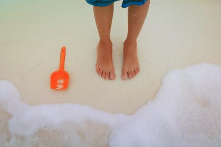 Feet of a child play on sand beach Фото со стока