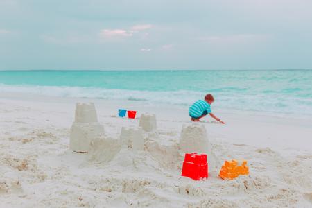 little boy building sand castle on beach Фото со стока