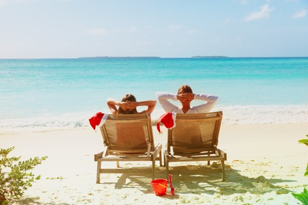 Christmas on beach -chair lounges and happy couple at sea Stock Photo