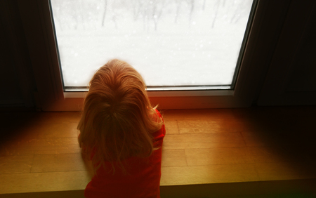 little girl looking through window, waiting for Christmas