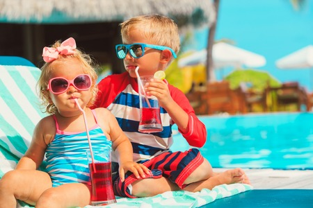 little boy and toddler girl drinking juices on beach Stock Photo