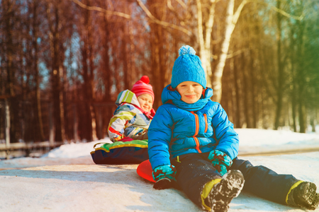 little boy and girl slide in winter snow