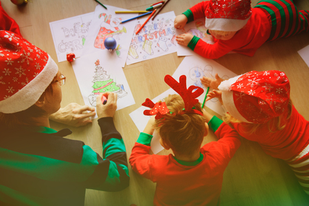 father and kids making Christmas crafts, family celebration