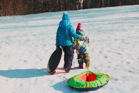 little boy and girl go for winter slide