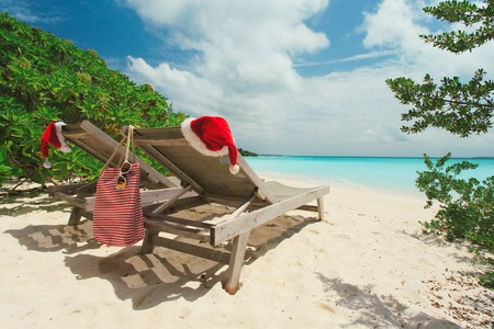 Christmas on beach -chair lounges with Santa hats at sea
