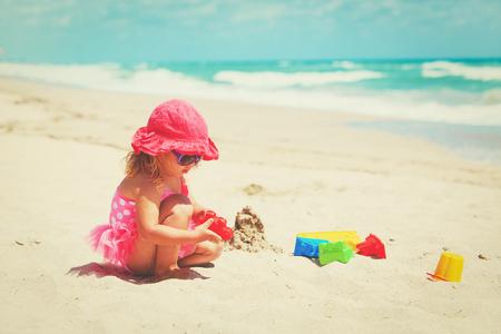 cute little girl play with sand on beach Reklamní fotografie - 91584224