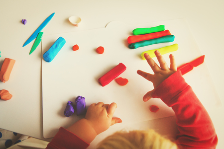 little baby play with clay molding shapes
