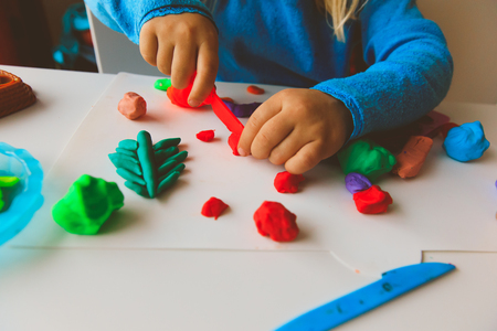 Child playing with clay molding shapes Imagens