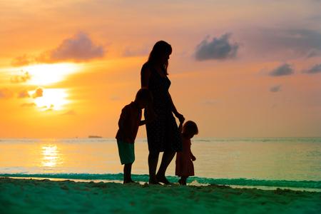 日没時にビーチを歩く母と2人の子供