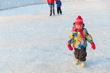 father with little daughter and son skating in winter