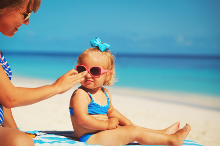 mother applying sunblock cream on daughter shoulder