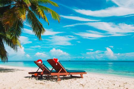 ビーチでのクリスマス - 海でサンタの帽子と椅子のラウンジ