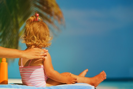 sun protection on beach - mother applying sunblock cream on daughter shoulder Stock fotó