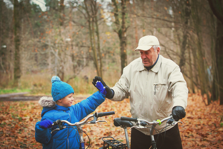 senior grandfather with grandson riding bikes in nature Stock Photo