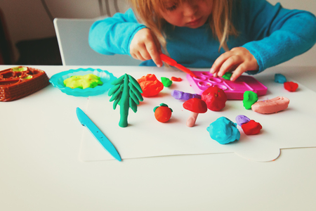 Child playing with clay molding shapes Banco de Imagens