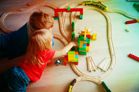 kids playing with toy railroad and trains