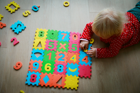 little girl play with numbers, learning math and calculations