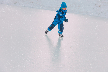 little boy skating on ice in winter Banco de Imagens - 93864907