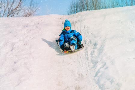 kids winter fun- little boy sliding in snow Banco de Imagens - 93864997