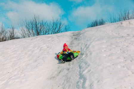 kids winter fun- little girl sliding in snow