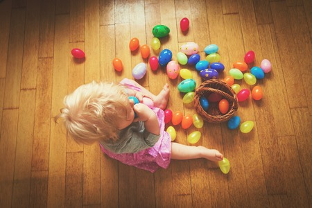 Klein meisje spelen met paaseieren Stockfoto - 93864237