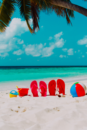 slippers, speelgoed en schelp op het strand