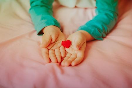 愛と家族。手に心を持つ小さな女の子