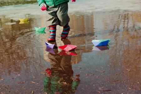 Criança brincando com barquinhos de papel na poça de água Foto de archivo - 94059946