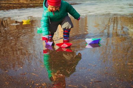 水たまりで紙ボートで遊ぶ子供