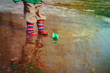 Criança brincando com barquinhos de papel na poça de água Foto de archivo - 94228647