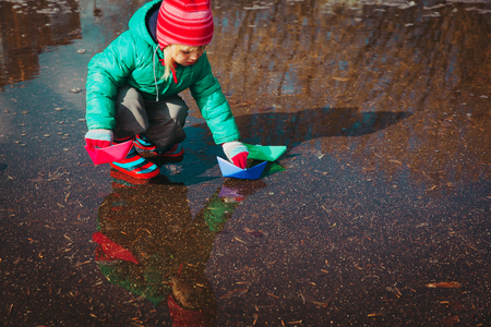 child playing with paper boats in water puddle