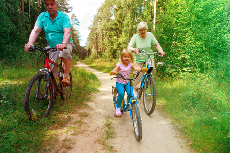 active senior couple with little granddaughter riding bikes in nature Stock Photo
