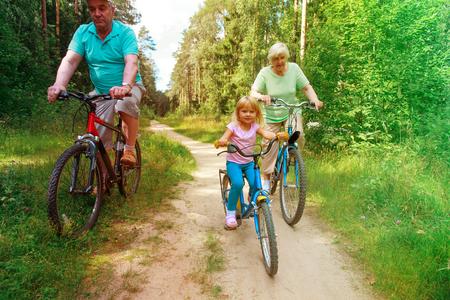 active senior couple with little granddaughter riding bikes in nature Reklamní fotografie