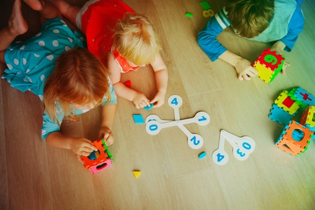 kids learning numbers, calculations, play with puzzle Фото со стока