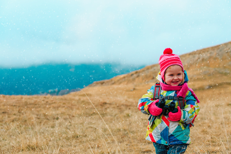 kids travel- little girl hiking in winter mountains