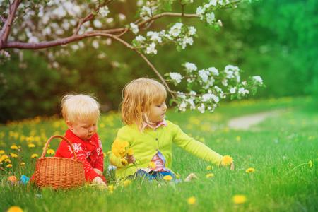 Glückliche Kinder auf Ostereiersuche im Frühjahr Standard-Bild - 94311767