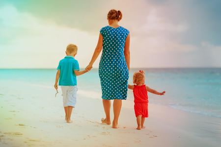 ビーチを歩く母と2人の子供