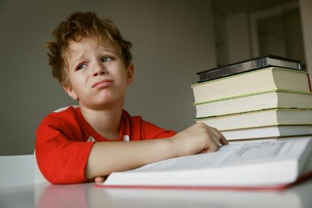 little boy tired stressed of reading, doing homework
