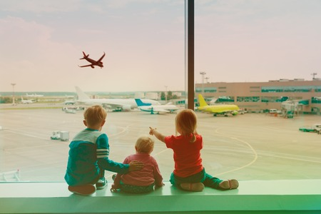 kids waiting for travel looking at planes in airport