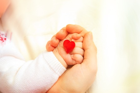 hands of mother and baby holding heart