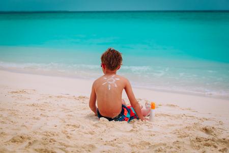 sun protection- little boy with suncream at tropical beach Reklamní fotografie