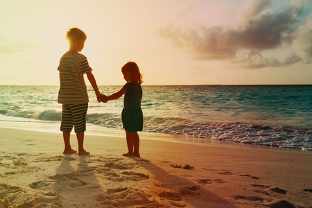 little boy and girl holding hands walk at sunset