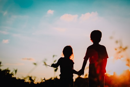 little boy and girl silhouettes holding hands at sunset Фото со стока