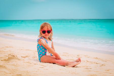 sun protection on beach- little girl applying sunblock cream on shoulder Reklamní fotografie