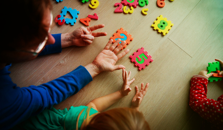 teacher and kids play with number puzzle