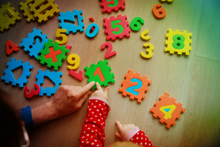 teacher and child play with number puzzle